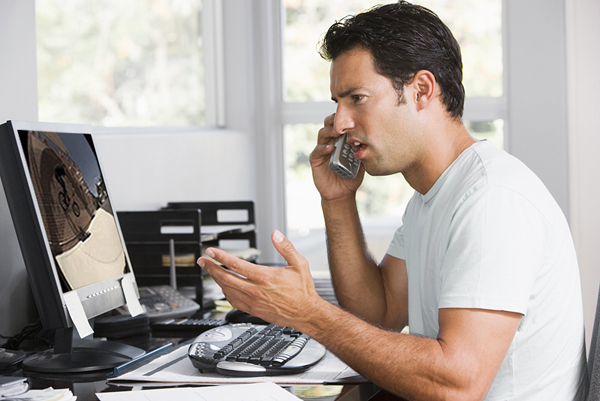 Man in home office on telephone using computer and frowning